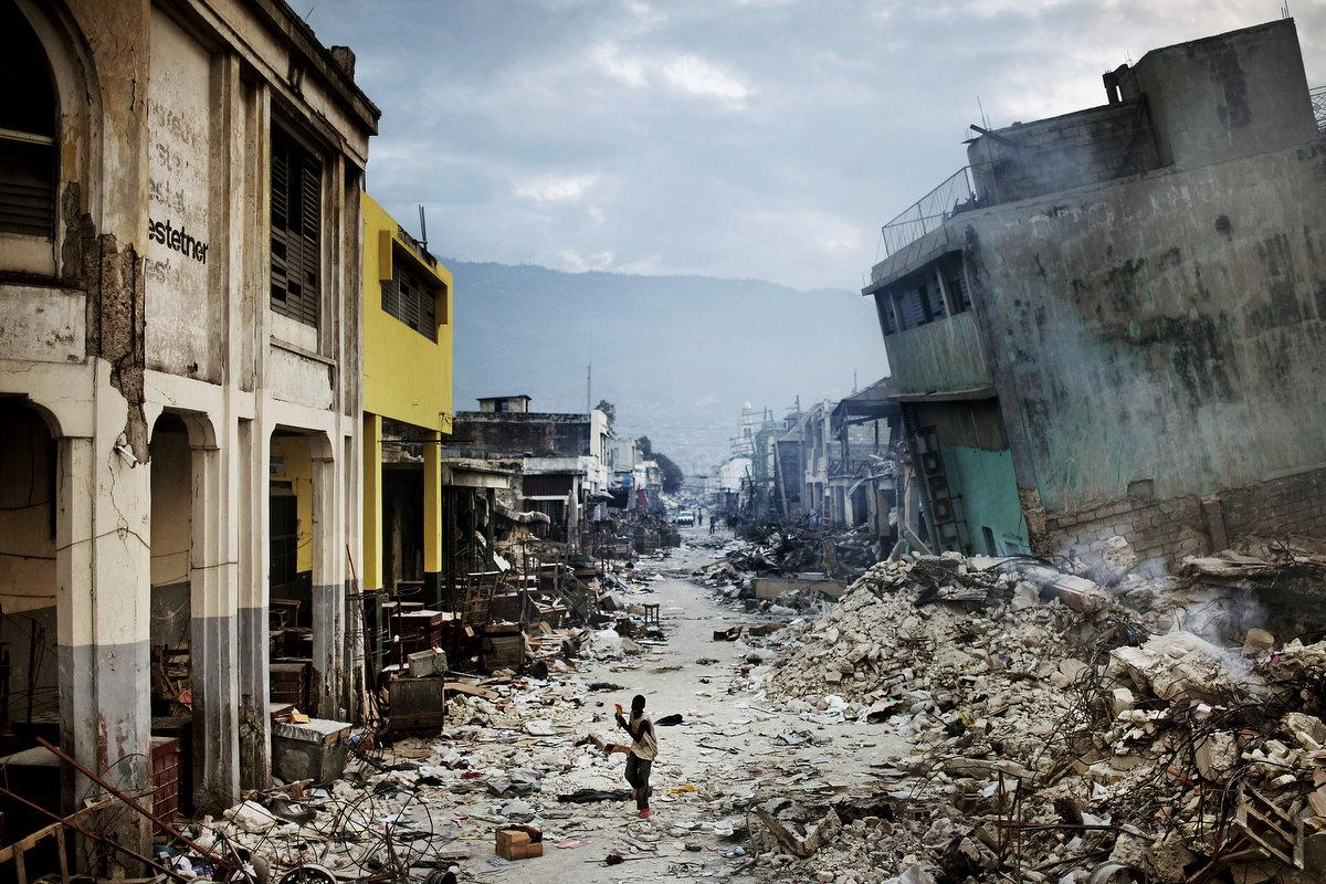 STORY: The January 12 earthquake in Haiti had catastrophic consequences, as it struck the most populated area in the country. The number of casualties rapidly rose to more than 200,000 people, and at least one million Haitians lost their homes. Structures of all kinds collapsed, from shantytowns to national landmarks. A year after the disaster the majority still lives in primitive tent camps around the city. In the weeks following the disaster sporadic violence, looting and gang-related gunfire broke out in downtown Port-au-Prince. The earthquake in Haiti could hardly have struck a worse place on the planet - the most basic necessities like water, food, electricity, communications, transportation and health care that is needed after a quake, were already inadequate before the quake hit. It has created a massive humanitarian crisis in the country routinely referred to as the poorest in the Western hemisphere. THIS IMAGE: A young boy escapes the violence that grew amid desperate looters, as gang-related gunfire broke out in downtown Port-au-Prince.